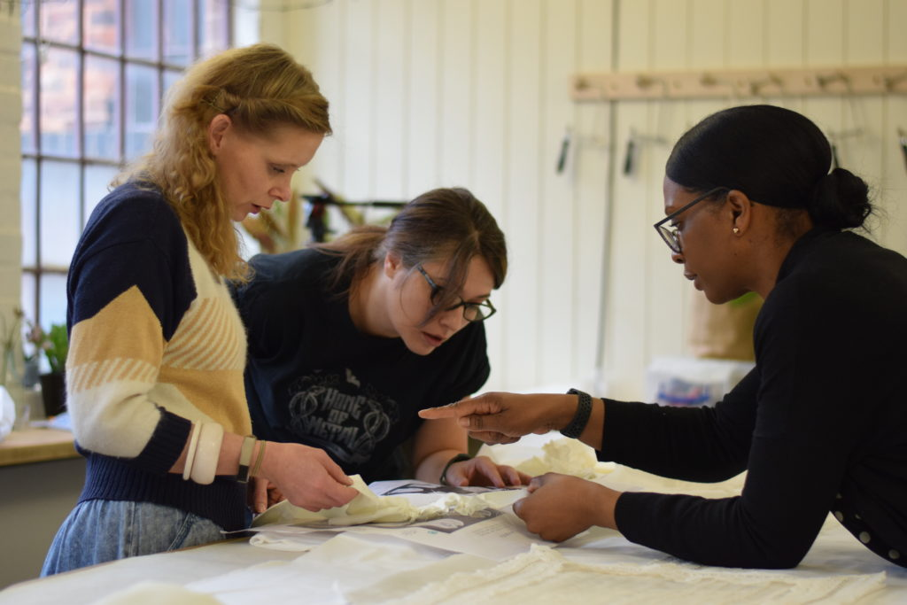 Three volunteers compare a shroud against catalogue images